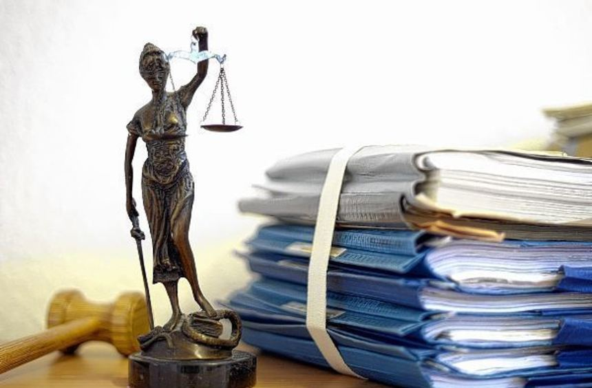 Ein Richterhammer, die Justitia und ein Stapel mit Gerichtsakten - zwei ehemalige Jurastudenten ...