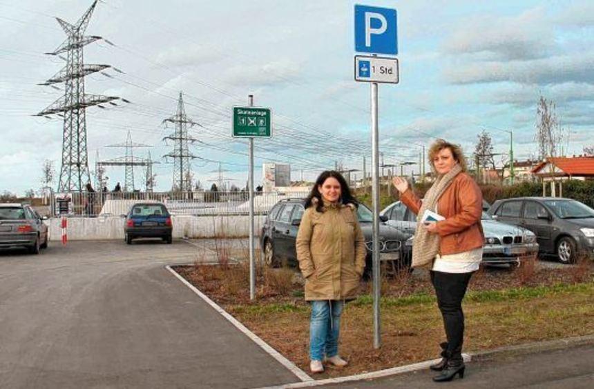 Berivan Ok (links) und Andrea Safferling mit dem neuen Schild am Parkplatz vor der Skaterbahn.