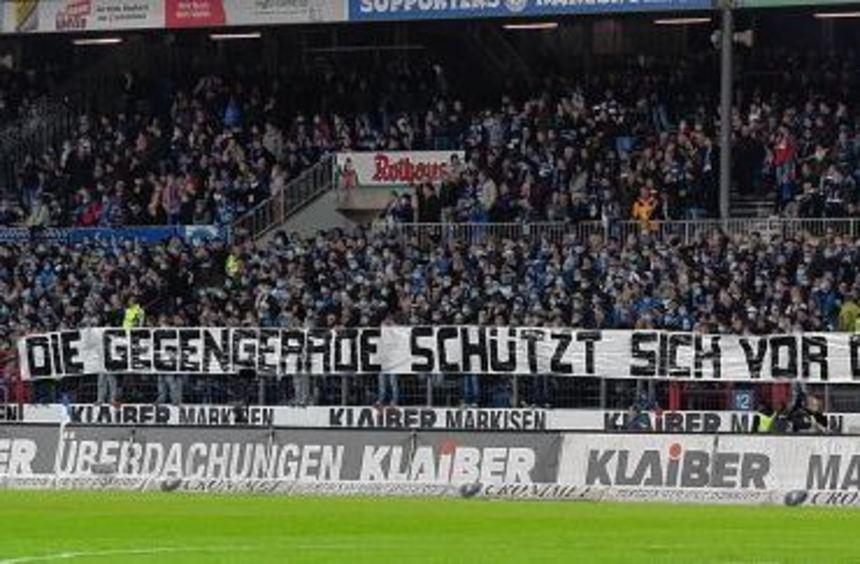 Zu Beginn des Spiels trugen viele Karlsruher Fans einen Mundschutz und verkündeten auf einem ...