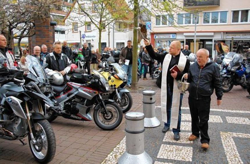 Vor der Apostelkirche segnet Kaplan Sebastian Lang Motorradfahrer und Zweiräder. Anschließend ...