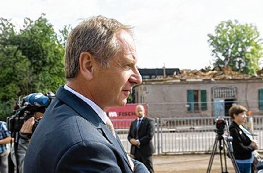 Innenminister Reinhold Gall vor den Überresten des Gebäudes.