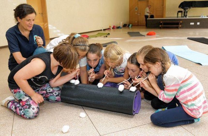 """Bei einer Übung pusten die Kinder symbolisch Wattebällchen über den """"Berg"""" hinweg. ..."""