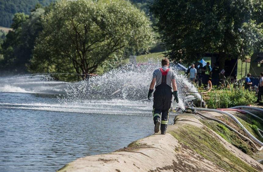 Ein Mitglied der Freiwilligen Feuerwehrläuft bei Eberbach auf einem Damm.