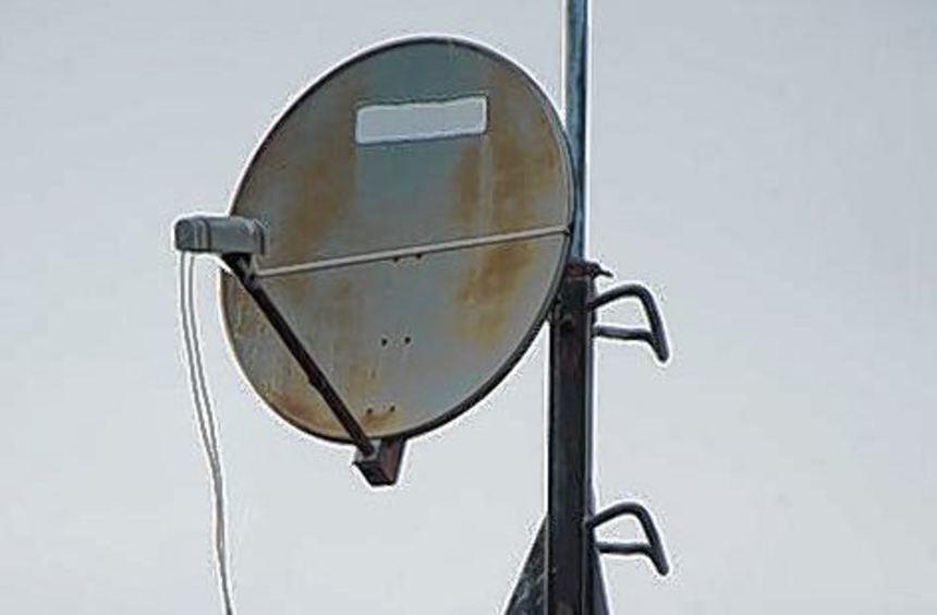 Eine Satellitenschüssel auf dem Dach eines Wohnhauses.
