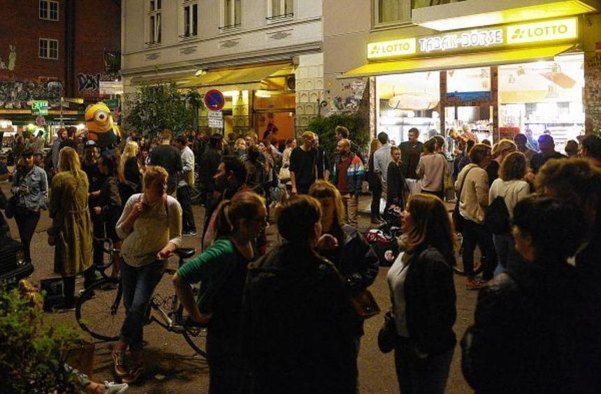 Junge Menschen stehen und sitzen in Hamburg nahe der Sternschanze nachts auf der Straße vor einem ...
