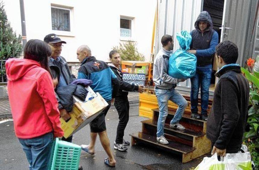 Hardheimer beladen einen Container mit Kleiderspenden, Asylbewerber packen mit an. Die ...