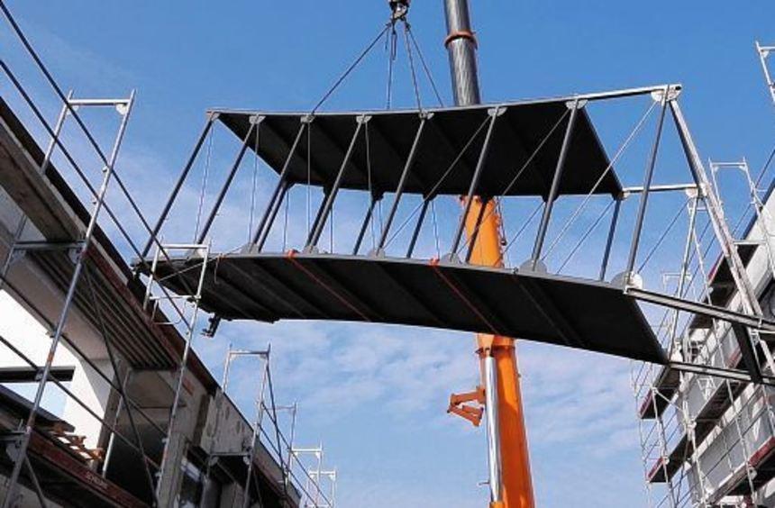 Millimeterarbeit: Passgenau wurde die Stahlbrücke zwischen die beiden Gebäude von ProxiVision ...
