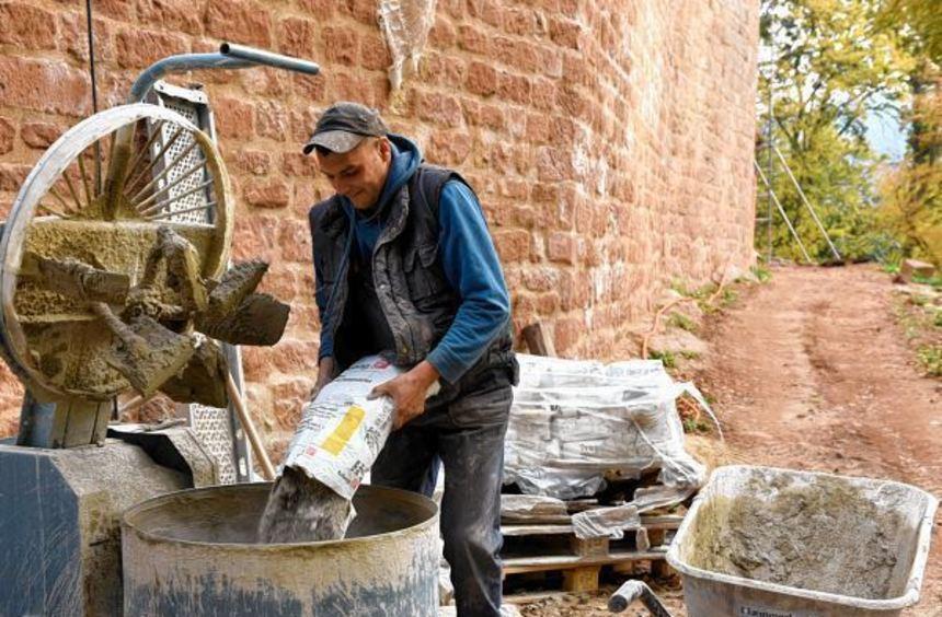Auf der Baustelle der Ruine Meistersel rührt ein Arbeiter frischen Mörtel an. Blick auf die Vorburg ...
