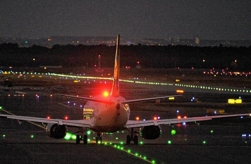 Landung bei Nacht: ein Flugzeug über dem Frankfurter Flughafen.