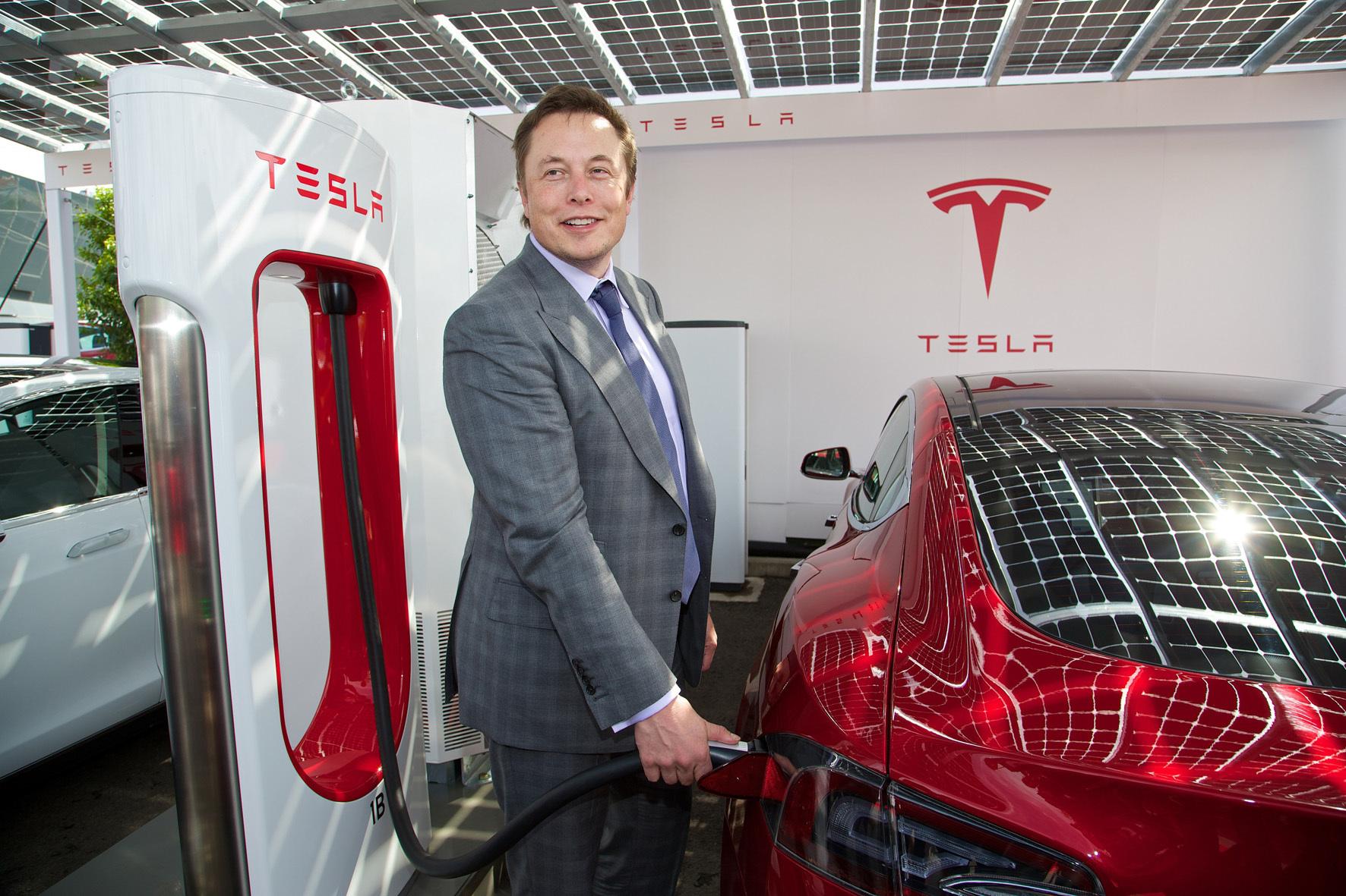 mid Düsseldorf - Hier tankt der Chef noch selbst: Tesla-CEO Elon Musk bei einer öffentlichkeitswirksamen Demonstration an einem Supercharger.