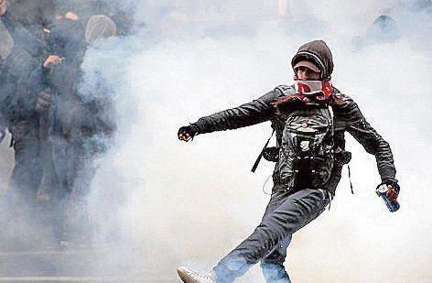 In Paris kickt ein Demonstrant eine Tränengaspatrone weg.