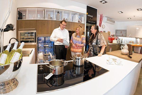 Geschäftsführer oliver schmidt zeigt den kundinnen sandra oehlenschläger mitte und sabine rathmann die vorzüge dieser küche