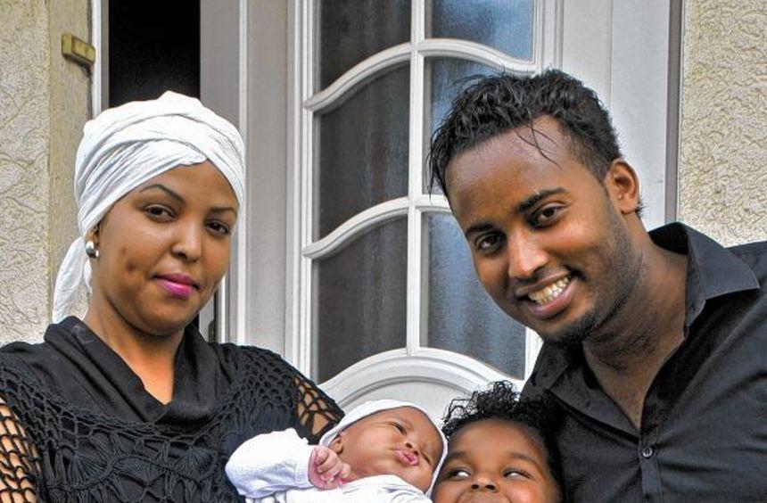 Glückliche Familie: Mutter Amina Omar hält Töchterchen Iqbaal auf dem Arm, Iqra freut sich im Arm ...