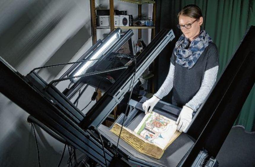 In der Heidelberger Uni-Bibliothek richtet Mitarbeiterin Christine Brenneis einen Band aus und ...