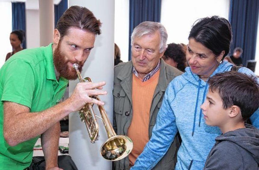 Musiklehrer Jörg Teichert (re.) macht den Besuchern in der Festhalle vor, wie man einen Ton aus der ...