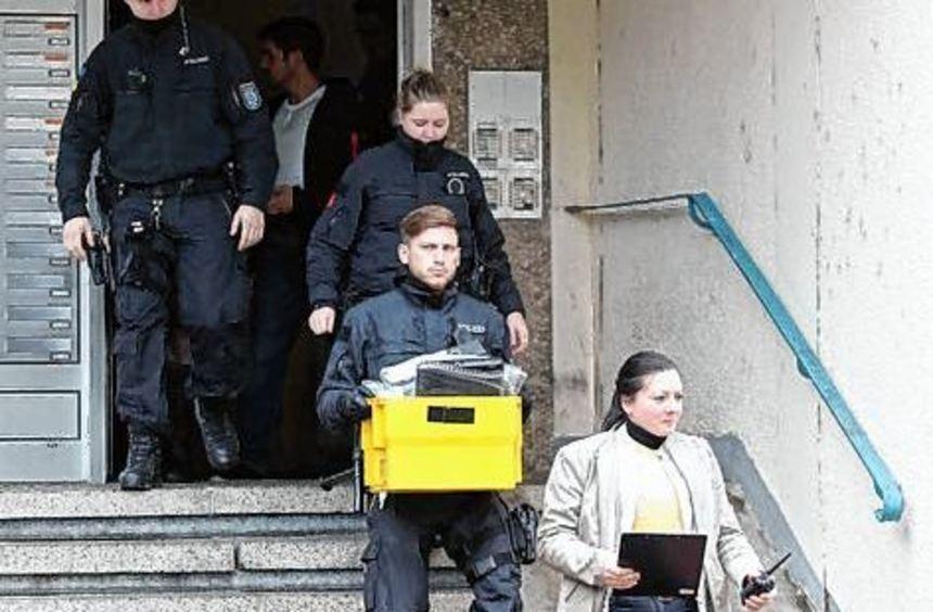 Polizisten verlassen während der Razzia ein Haus in Jena.