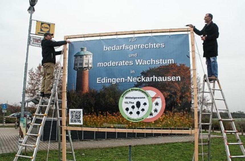 Stefan Brendel und Enzio Ermarth folgen einer Anordnung des Landratsamtes und bauen ihr Großplakat ...