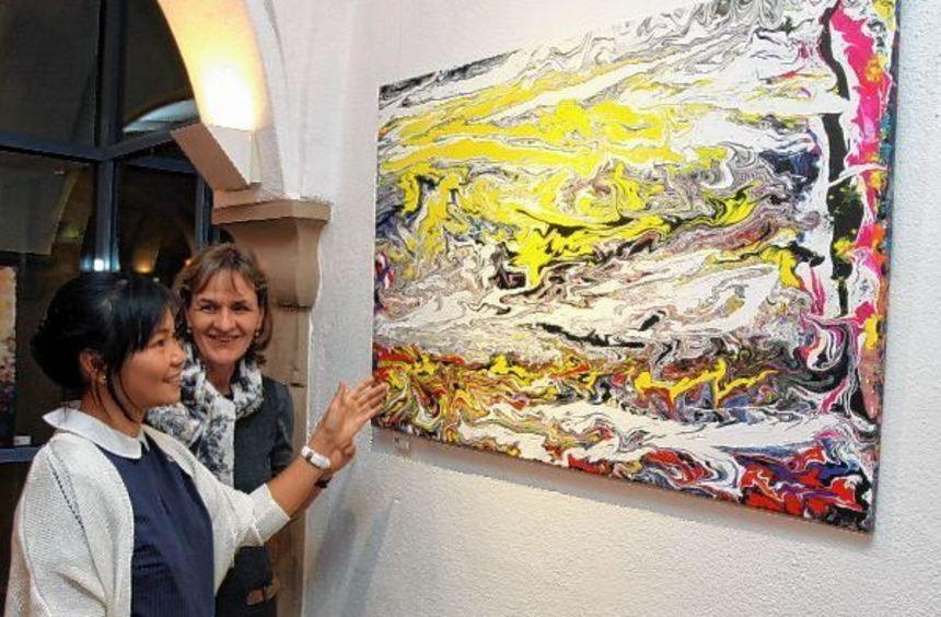 Eine einzige Farbexplosion: Künstlerin Chi Phuong Bothe (vorne) erklärt Interessierten gerne ihre ...