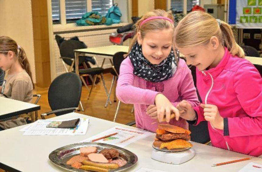 Lernwerkstatt im Landratsamt: Die Grundschülerinnen wiegen die Menge an Fleisch und Wurst ab, die ...