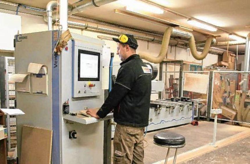 Schreinermeister Tobias Herbel (l.) bedient die moderne CNC-Fräsmaschine in der Schreinerei Keller. ...