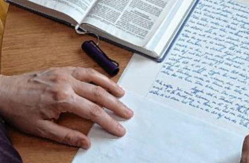 Das sind die Hände von Pfarrerin Julia Bokowski, wie sie gerade dabei ist, eine Bibelseite ...