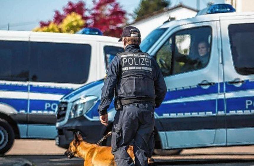 Ein Polizist läuft mit einem Spürhund an Einsatzfahrzeugen in Rottenburg am Neckar ...
