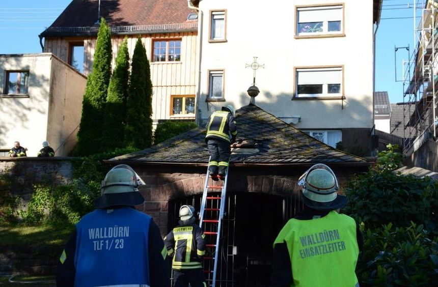 Feuerwehrleute untersuchen das Dach der ausgebrannten Kapelle.