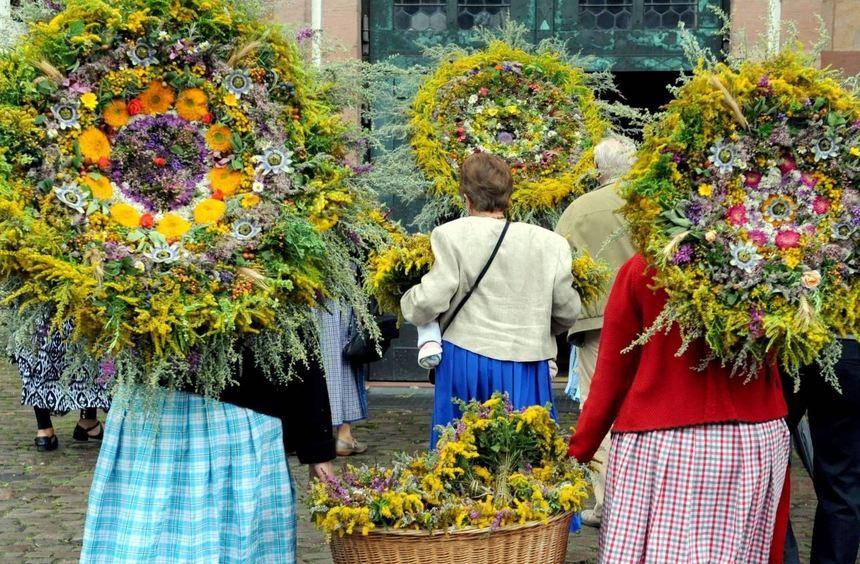 Frauen tragen riesige, im Biedermeier-Stil gebundene Sträuße aus Kräutern zur Weihe in die Kirche. ...