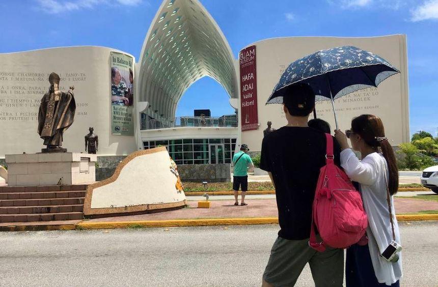 Touristen spazieren in Hagatna auf der Insel Guam entlang der Dulce Nombre de Maria Kathedrale. ...