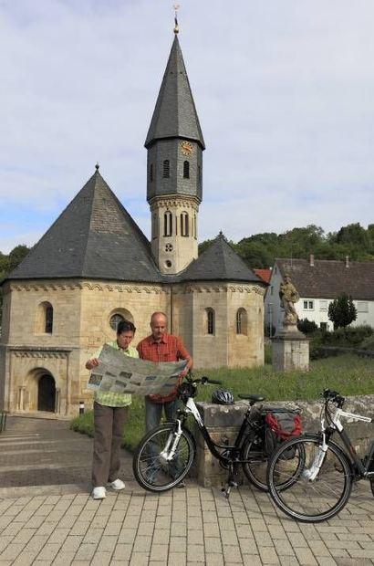 Radfahrer vor der St.-Achatius-Kapelle in Grünsfeld.