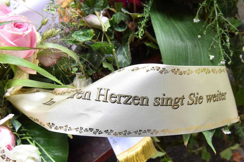 Freunde, Familie und Bewunderer legten Blumenschmuck...