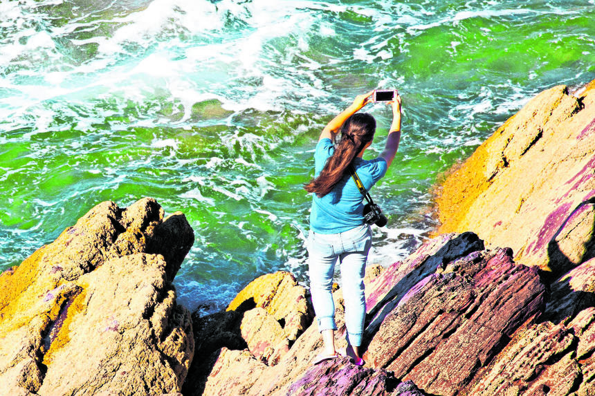 A woman taking a selfie with her phone in a dangerous position on rocks next to in coming tide at Freathy Beach at Whitsand Bay, Cornwall