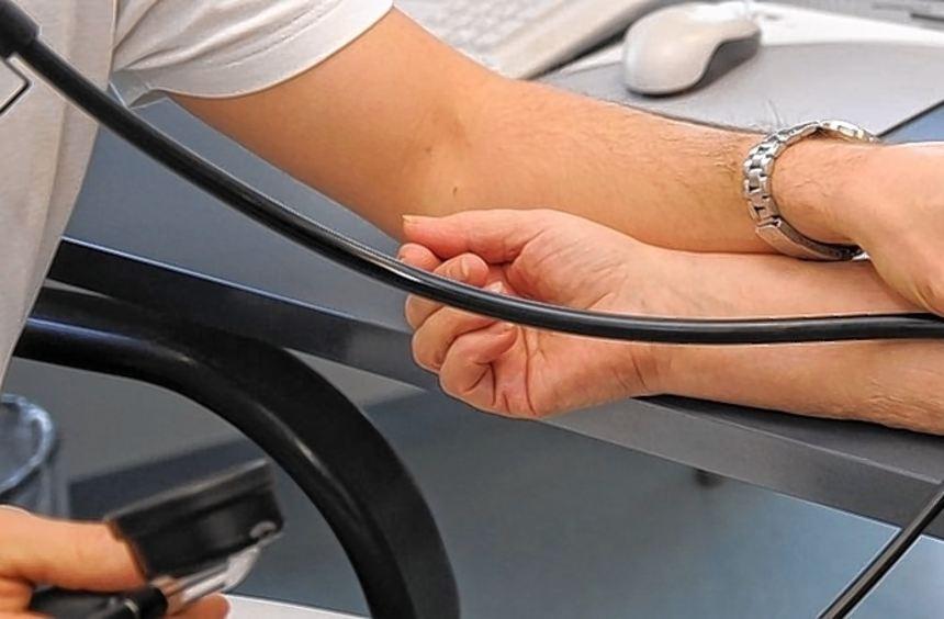 Ein Hausarzt misst bei einer Patientin den Blutdruck.