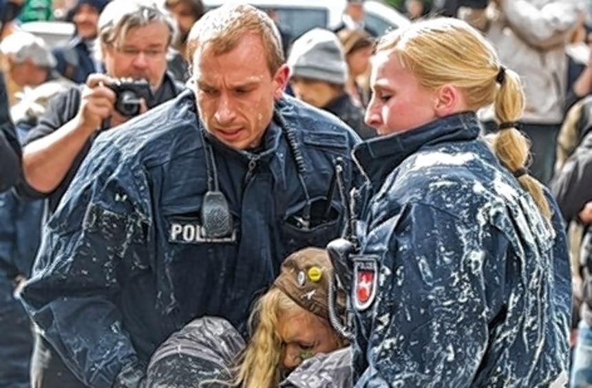 Polizisten tragen eine Demonstrantin aus der Zeltstadt.