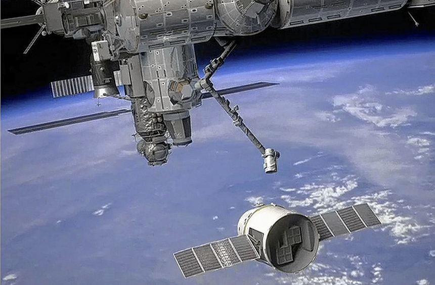 """Die Computerillustration der NASA zeigt eine """"Dragon""""-Kapsel (unten), die vom Roboterarm der ISS ..."""