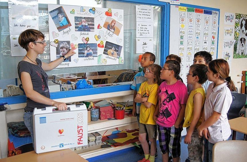 """Lehrerin Sandra Schwarz mit einer dritten Klasse vor Plakaten des """"Faustlos""""-Projekts."""