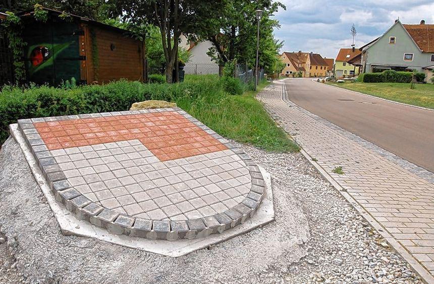 Mit roten und weißen Pflastersteinen wurde an beiden Ortseingängen das Finsterlohrer Ortswappen ...