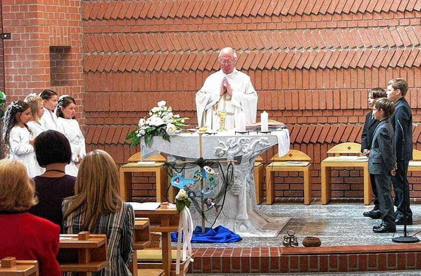 Sieben Kinder aus Hüttenfeld feierten mit Pfarrer Peter Hammerich ihre Erstkommunion in der ...