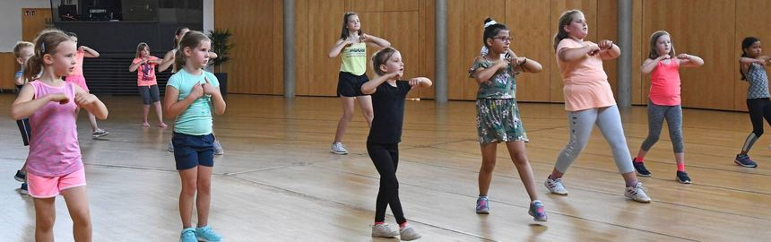 Die Arme rollen und ein Schritt nach vorne: Die Kinder machen die Bewegungen nach, die ihnen ...