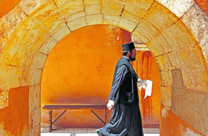 Ein Mönch eilt durch den Kreuzgang des Klosters Agia Triáda Jagarolou mit dem prächtigen ...