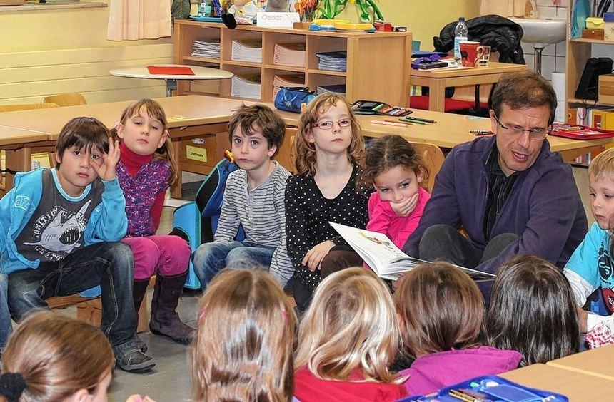 Pfarrer Andreas Maier legt sich beim Vorlesen ordentlich ins Zeug, um die Kinder der Jahnschule für ...