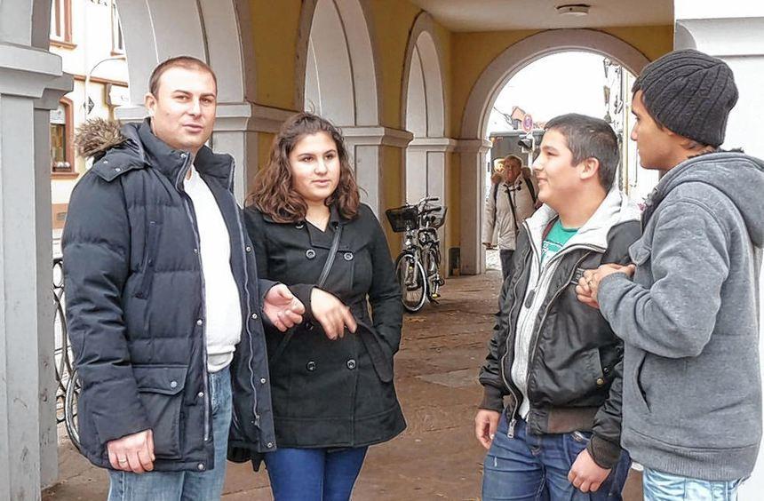 Alfred Zimbakov (links) vor Ort am Alten Rathaus im Gespräch mit jungen Leuten aus Seckenheim.