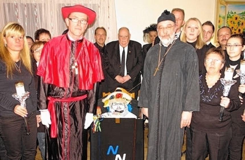 Pfarrer Karl-Heiz Huft (rechts) trägt mit Trauernden Prinz Jokus zu Grabe.