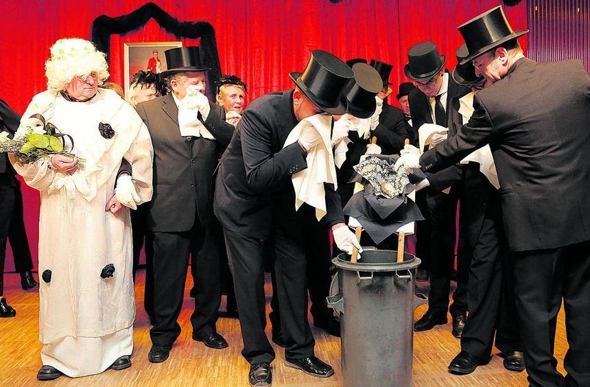 Der Trauerzug der schwarz gekleideten Narren lässt die Fastnacht in die Mülltonne gleiten. Als ...