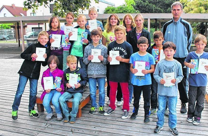 Präsentieren stolz ihre Ehrenurkunden: die 14 Grundschüler und ein Hauptschüler der Schule in den ...