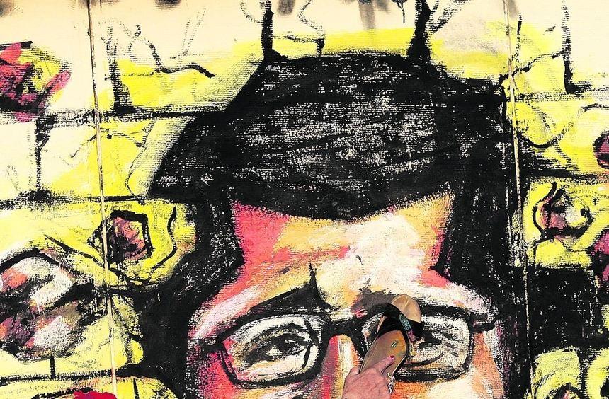 Wut auf den Präsidenten: Mit einem Schuh traktiert eine Frau in Kairo eine Karikatur von Mursi.