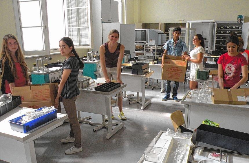 Schüler und Lehrer packen im Chemiesaal der Marie-Curie-Realschule die Umzugskisten aus (links). ...