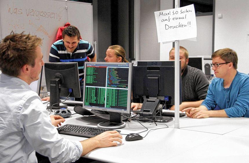 """Matthias Luft (vorne) und Sebastian Lekies und Florian Barth (v.l.) im """"Hackerkeller""""."""