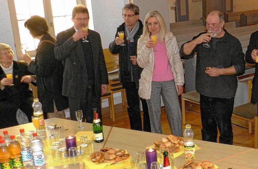 Mit Sekt stoßen die Mitglieder der evangelischen Kirchengemeinde Hüttenfeld auf gleich zwei Dinge ...