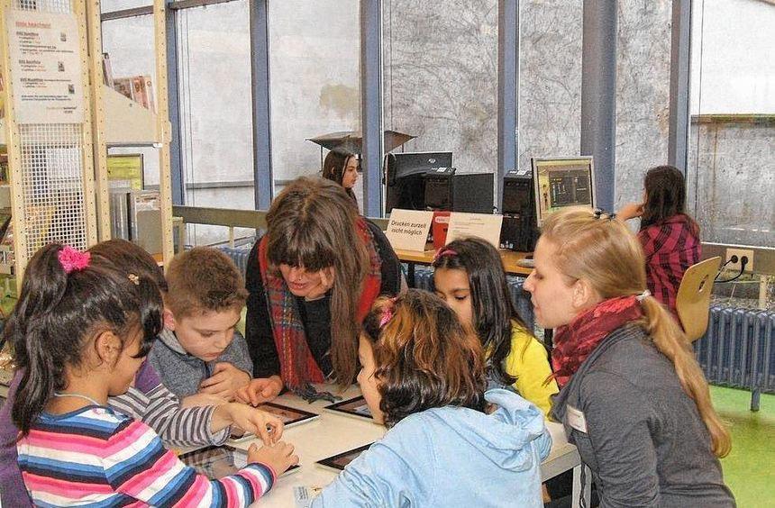 Begeisterte Kinder probieren sich an den ersten digitalen Büchern, einem Angebot der ...